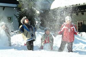 Kinder beim Schneemannbauen, Dorf Schönleitn