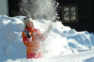 Kind schmeißt Schnee in die Luft, Hoteldorf Schönleitn