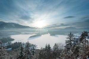 Aussicht auf verschneiten, zugefrorenen Faaker See