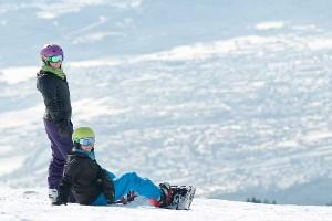 Kinder bei kurzer Rast vom Snowboard Tag