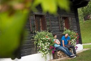 Pärchen auf Bank vor Bauernhaus, Dorf Schönleitn