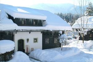 verschneites Bauernhaus im Dorf Schönleitn