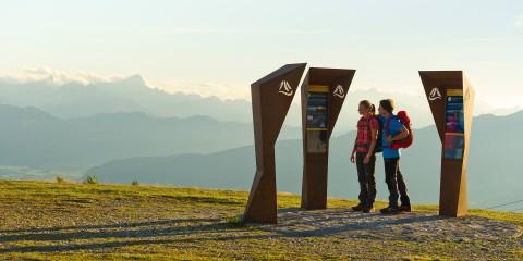 Wanderer vor Infotafeln am Berg