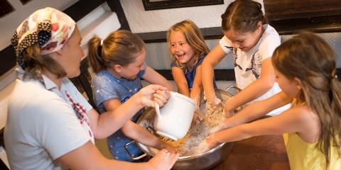 Kinder beim Brotbacken im Hoteldorf Seeleitn