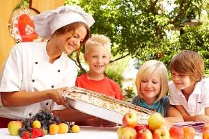 Köchin präsentiert Kindern frischen Apfelstrudel am Genussplatz